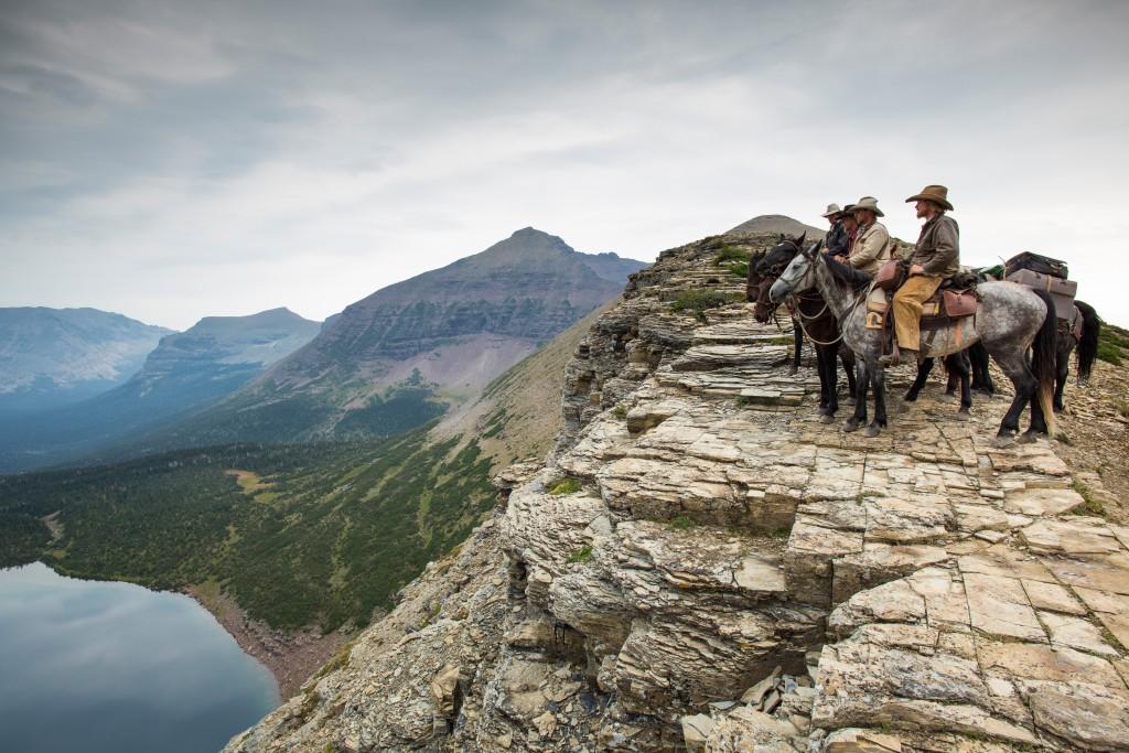 Vier Cowboys auf ihren Pferden am Abgrund eines Steilhangs blicken in die Weite.